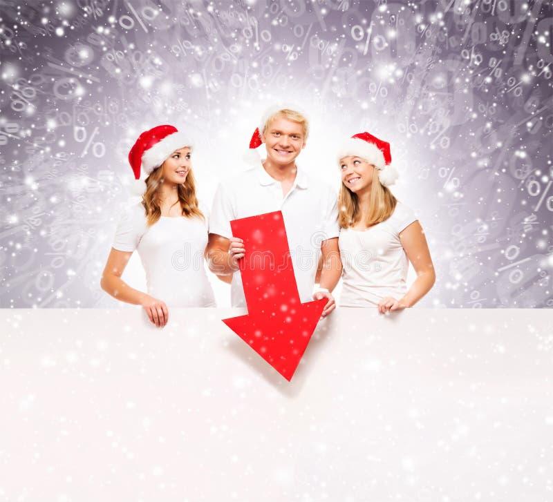 Três adolescentes felizes em chapéus do Natal que apontam em uma bandeira imagens de stock