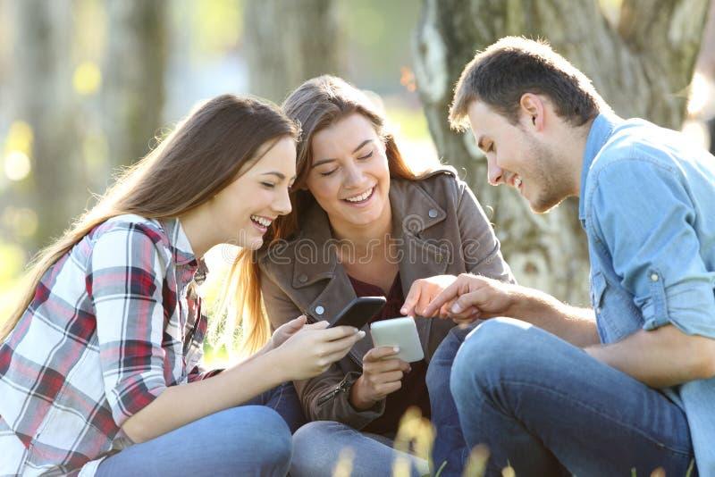 Três adolescentes que compartilham na linha índice em telefones fotografia de stock royalty free