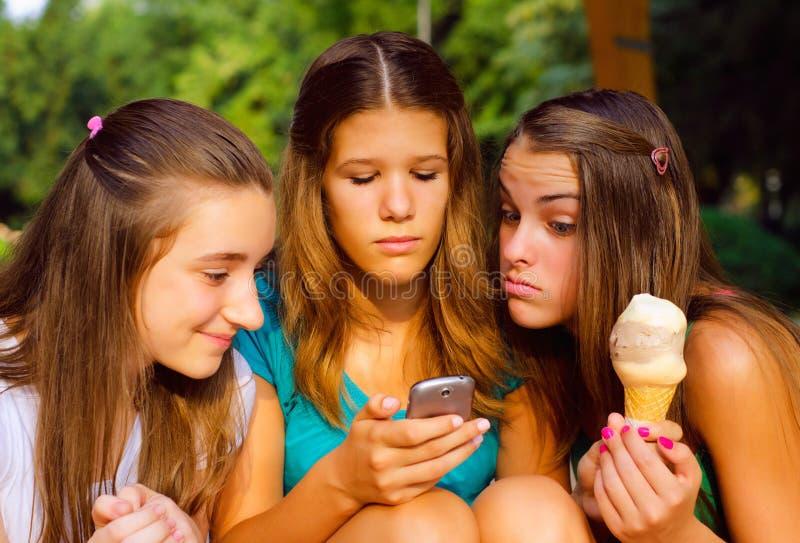 Três adolescentes que têm o divertimento exterior imagens de stock