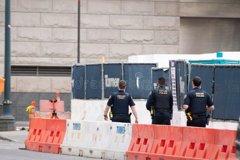 Três agentes da polícia de portland que patrulham a rua fotos de stock