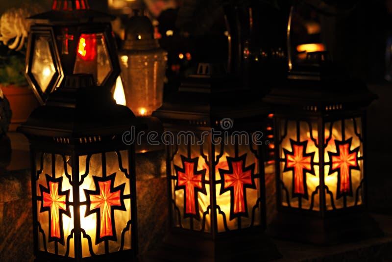 Três amarelos e velas graves vermelhas em um cemitério na noite imagem de stock royalty free