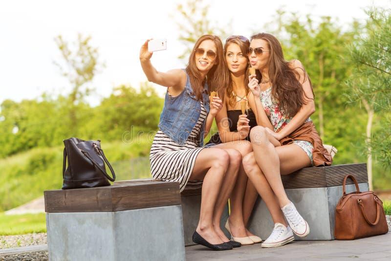 Três amigas bonitas fazem a foto de Selfie em um banco imagens de stock royalty free