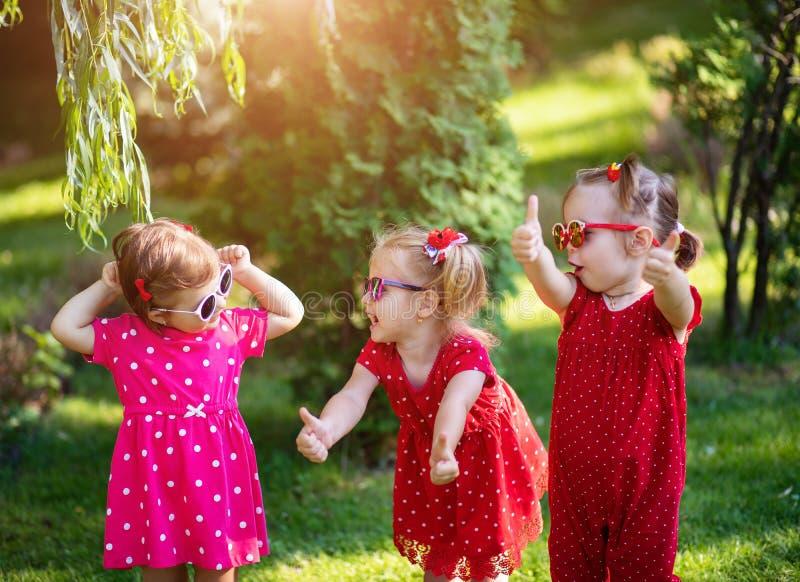 Três amigas pequenas bonitos que têm o divertimento na jarda a vista da mostra da menina manuseia a sorte ascendente e boa vestid imagens de stock royalty free