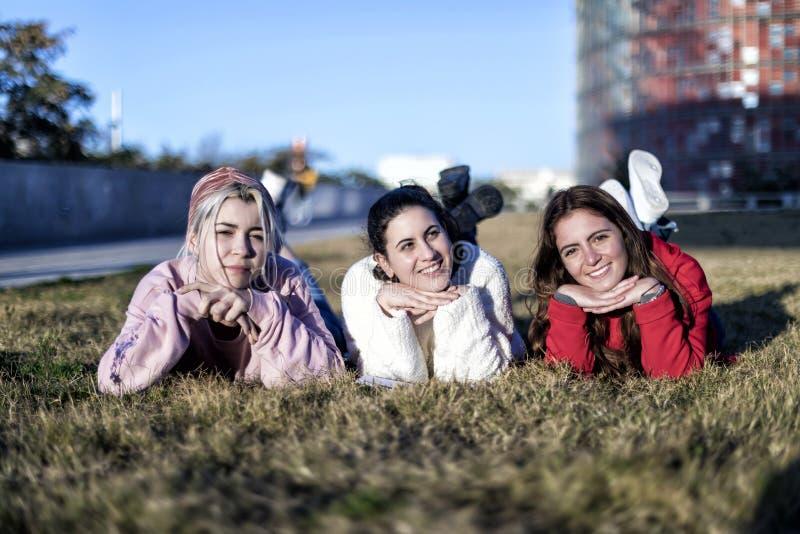 Três amigas que encontram-se na grama em um parque no outono fotografia de stock