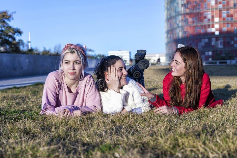 Três amigas que encontram-se na grama em um parque no outono imagens de stock
