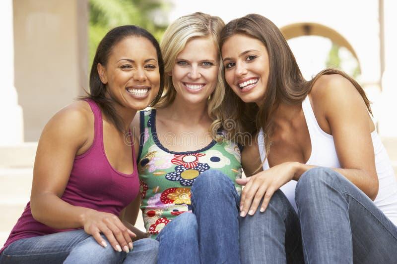 Três amigas que sentam-se em etapas do edifício imagens de stock royalty free