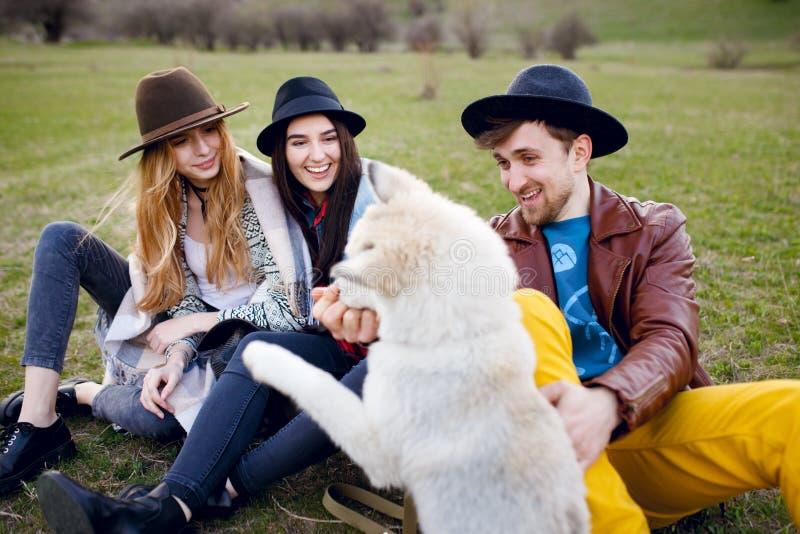 Três amigos à moda novos bonitos passam o tempo fora junto com seu cão ronco que senta-se na grama verde imagens de stock royalty free
