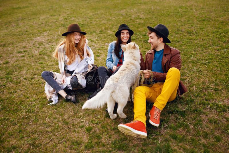 Três amigos à moda novos felizes passam o tempo fora junto com seu cão ronco que senta-se na grama verde fotografia de stock royalty free