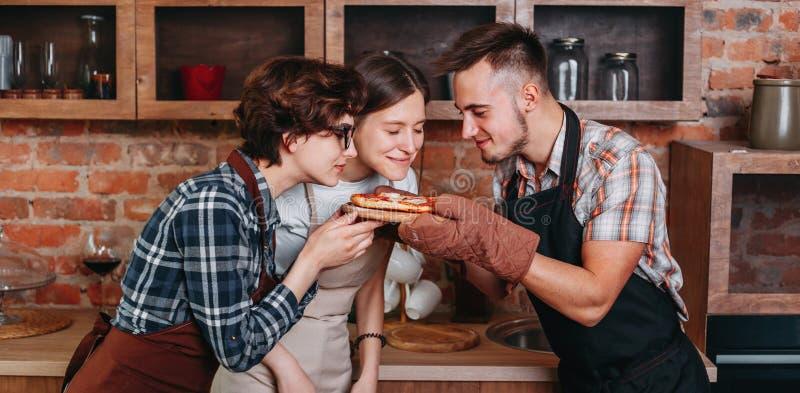 Três amigos apreciam o cheiro da pizza recentemente cozida fotografia de stock royalty free