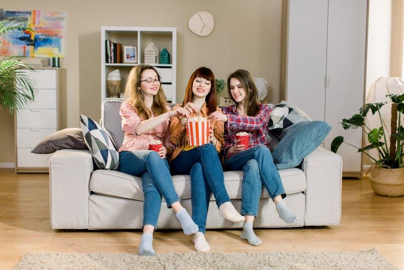 Três amigos bonitos das jovens mulheres em casa que comem a pipoca que senta-se no sofá cinzento junto e no riso Partido das mulh imagem de stock royalty free