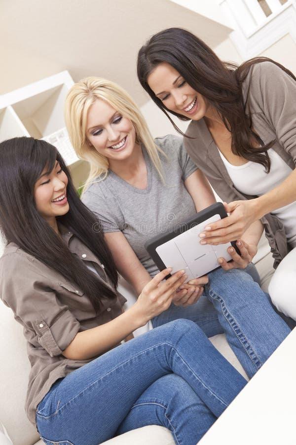 Três amigos bonitos das mulheres com computador da tabuleta fotografia de stock royalty free