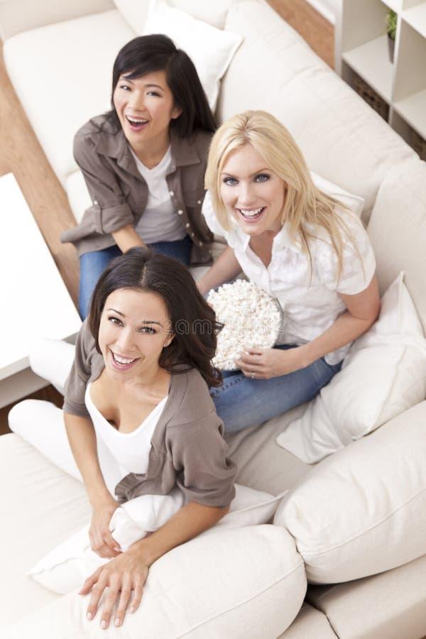 Três amigos bonitos das mulheres que comem a pipoca fotografia de stock