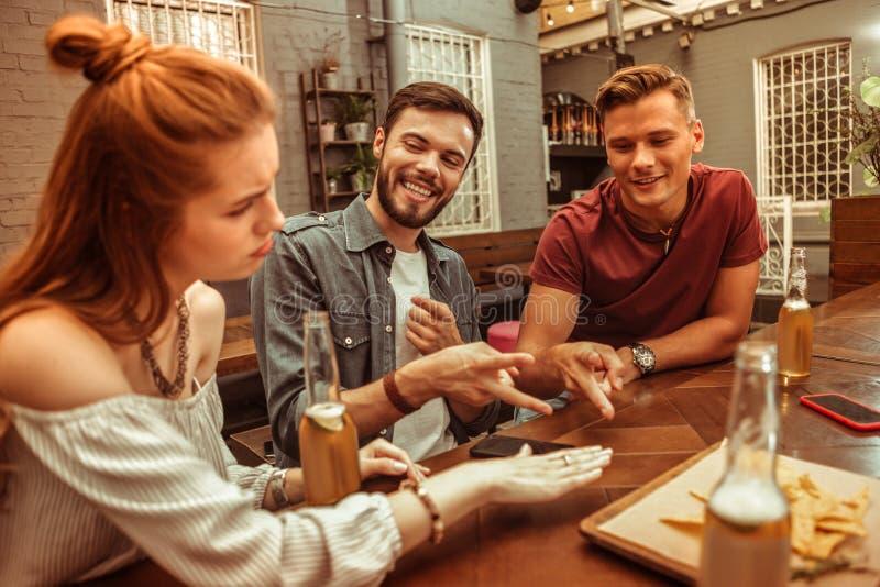 Três amigos bonitos deapelo do novo-adulto que jogam o jogo das rocha-papel-tesouras fotos de stock
