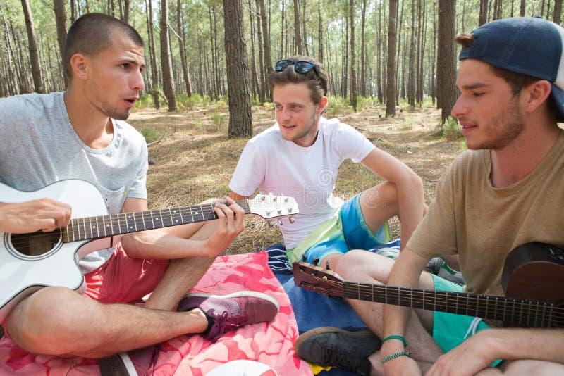 Três amigos com a guitarra que senta-se na cobertura na floresta imagens de stock