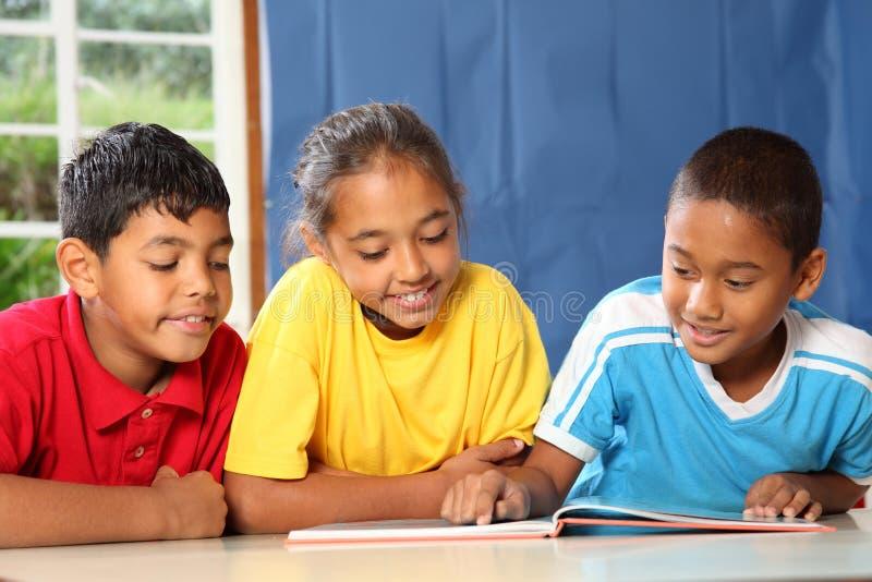 Três amigos da escola preliminar que lêem e que aprendem imagem de stock royalty free