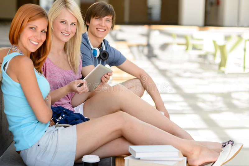Três amigos da estudante universitário com sorriso da tabuleta fotos de stock