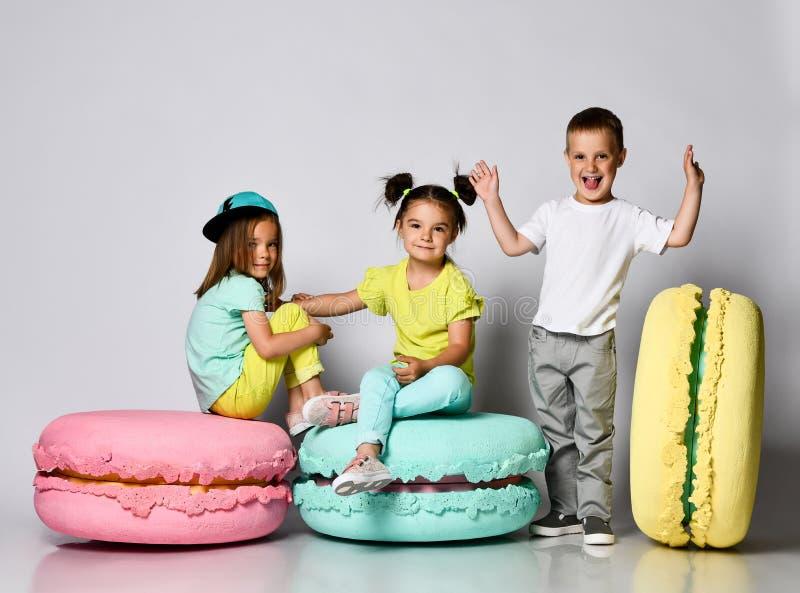 Três amigos das objetivas triplas - duas meninas e um menino na roupa brilhante têm o divertimento nos macarons da decoração da s imagens de stock royalty free