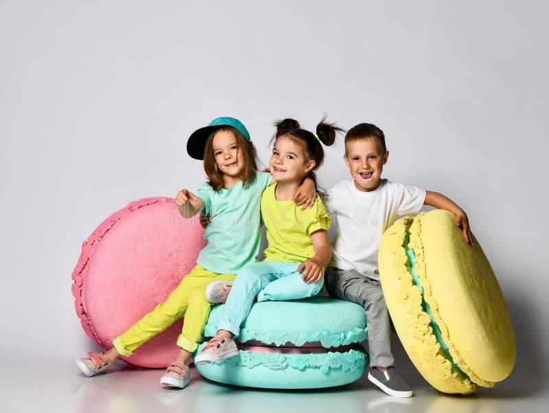 Três amigos das objetivas triplas - duas meninas e um menino na roupa brilhante têm o divertimento nos macarons da decoração da s fotografia de stock