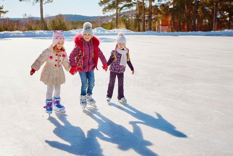 Três amigos de menina aprendem patinar Recreação exterior foto de stock