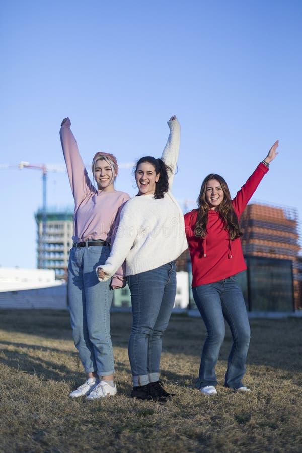 Três amigos de meninas adolescentes felizes que saltam altamente no céu azul no fundo do ar livre do verão foto de stock royalty free