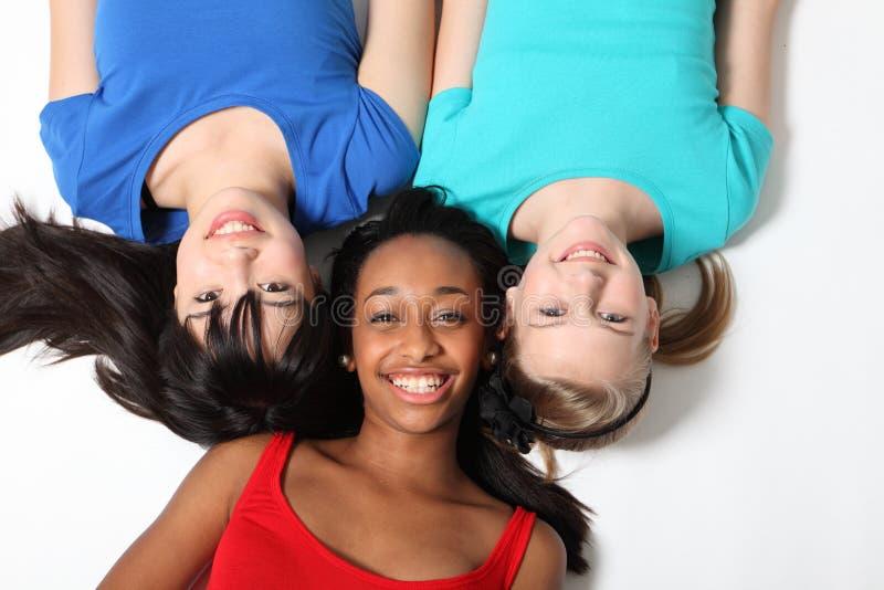 Três amigos do adolescente da raça misturada no assoalho foto de stock