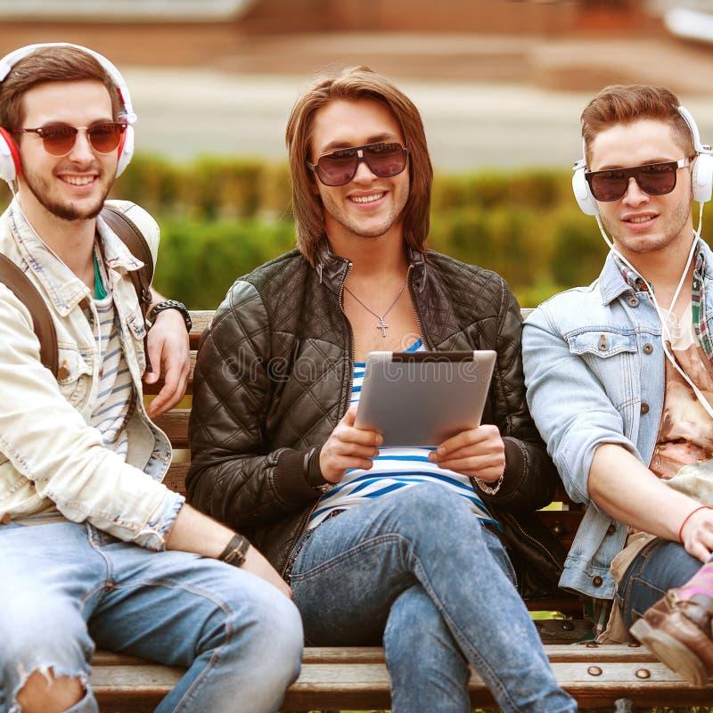 Três amigos dos homens novos que usam o tablet pc no parque imagem de stock