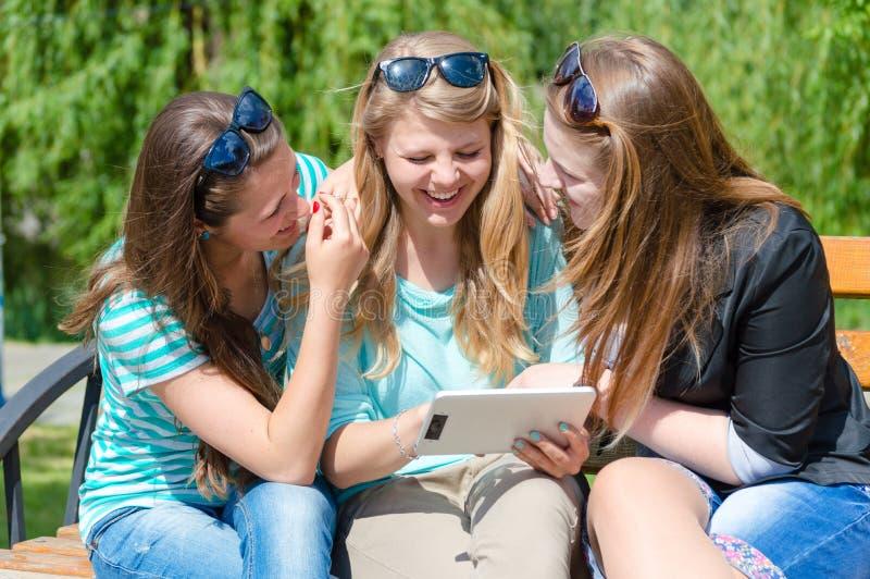 Três amigos e tablet pc felizes das jovens mulheres do smilng imagem de stock