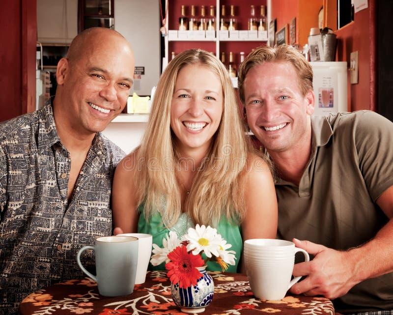 Três amigos em uma casa de café imagens de stock royalty free