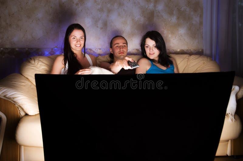 Três amigos estão prestando atenção à tevê foto de stock