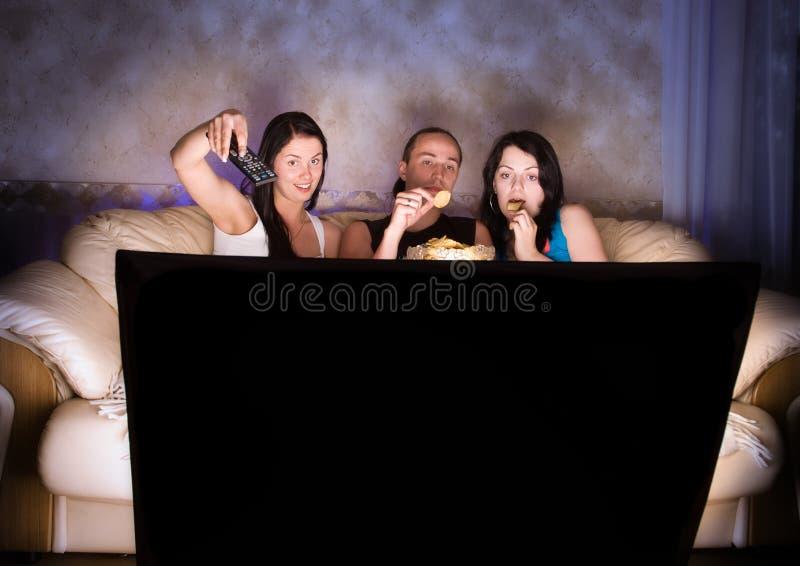 Três amigos estão prestando atenção à tevê imagem de stock royalty free