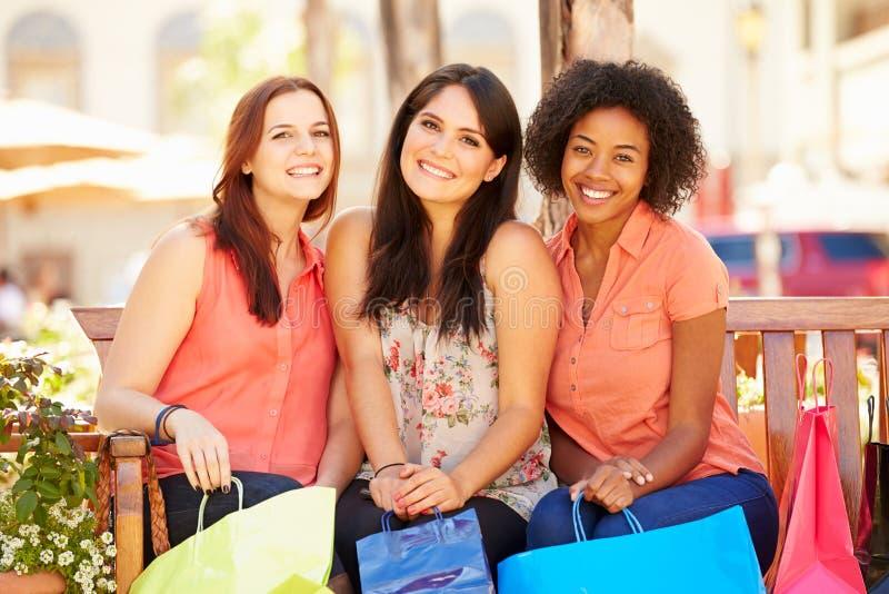 Três amigos fêmeas com os sacos de compras que sentam-se na alameda foto de stock
