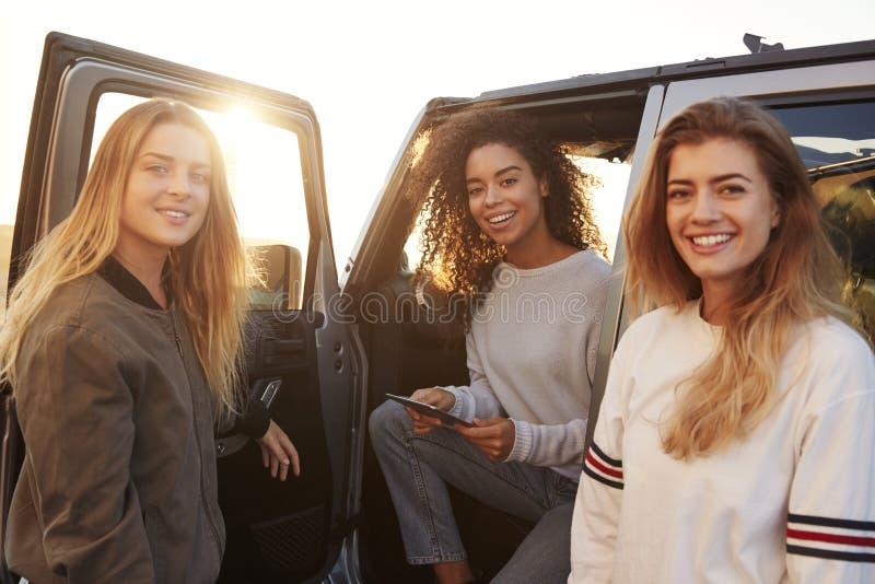Três amigos fêmeas em uma viagem por estrada usando uma tabuleta, fim acima imagens de stock