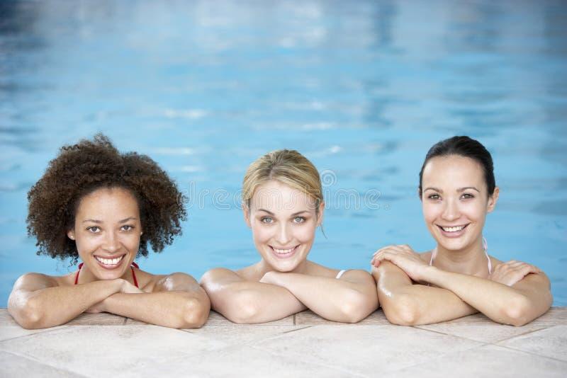 Três amigos fêmeas na piscina fotografia de stock royalty free