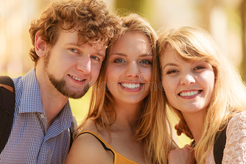 Três amigos felizes dos jovens exteriores imagem de stock
