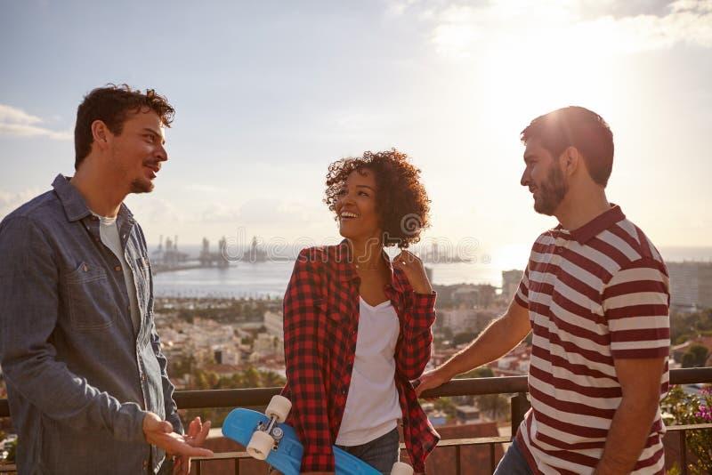 Três amigos frescos que riem em uma ponte imagens de stock