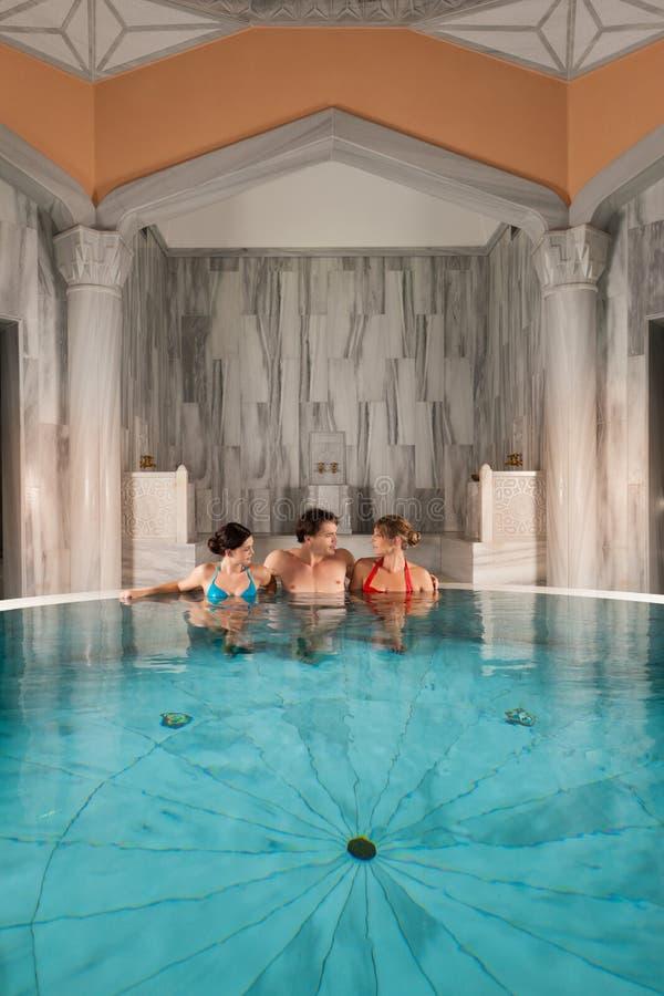 Três amigos na piscina ou no banho térmico foto de stock