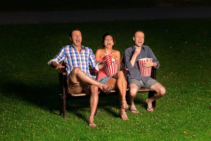 Três amigos no cinema exterior fotografia de stock royalty free