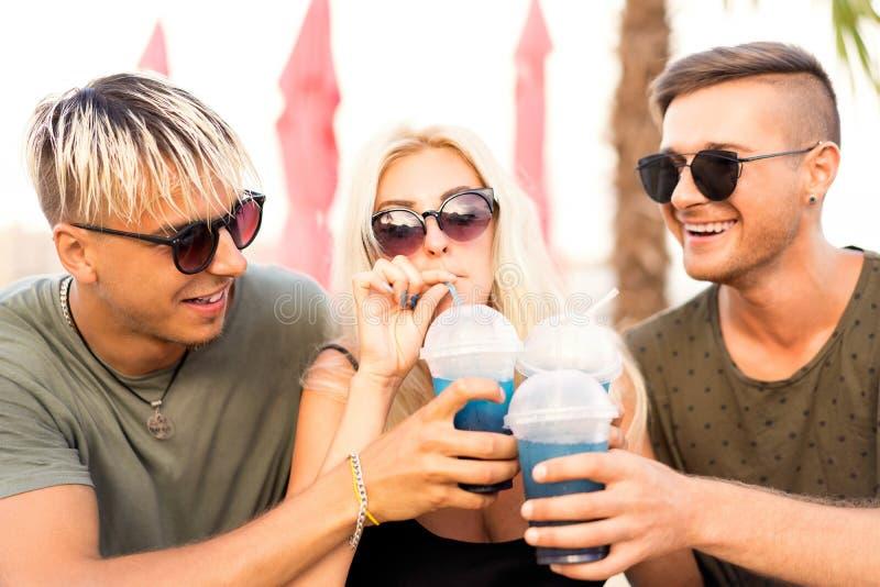 Três amigos no divertimento bebendo dos cocktail da praia imagens de stock