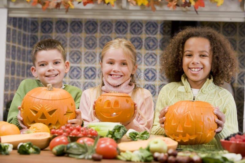 Três amigos novos em Halloween com abóboras foto de stock royalty free