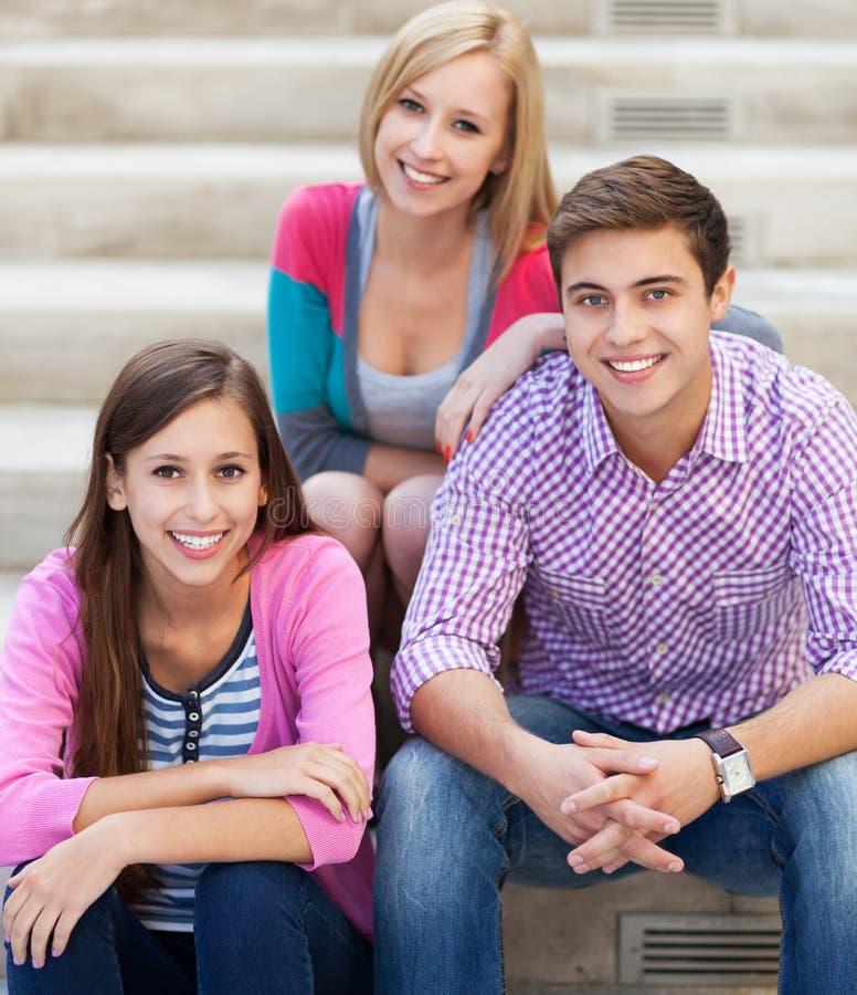Três amigos novos que sentam-se junto