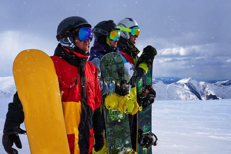 Três amigos olham snowboarders dianteiros corajosamente imagem de stock royalty free