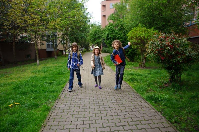 Três amigos pequenos vão à escola imagem de stock