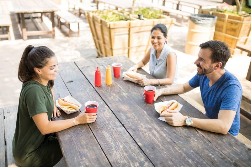 Três amigos que comem cachorros quentes foto de stock