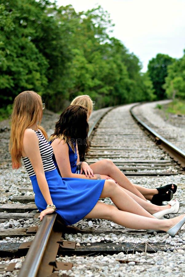 Três amigos que esperam o trem fotos de stock