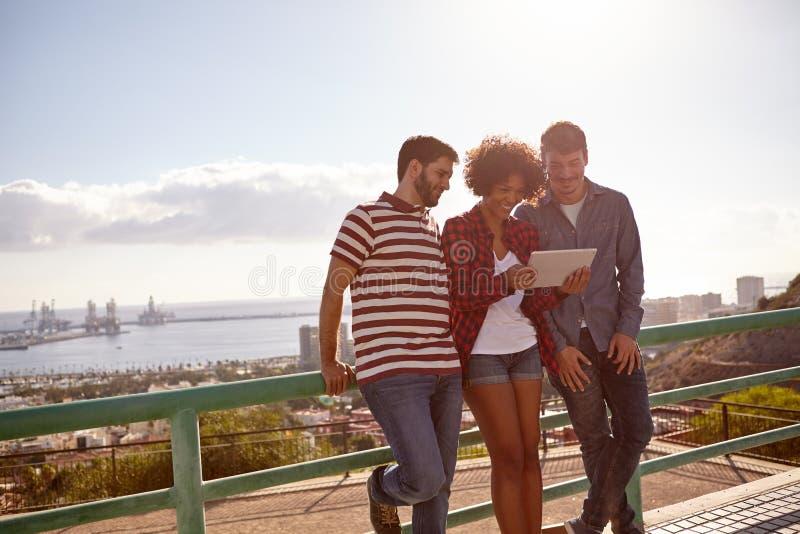 Três amigos que inclinam-se contra uns trilhos fotografia de stock royalty free