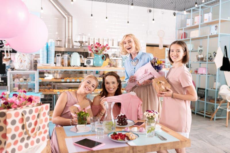 Três amigos que juntam-se a seu colega de antecipação na padaria imagem de stock royalty free