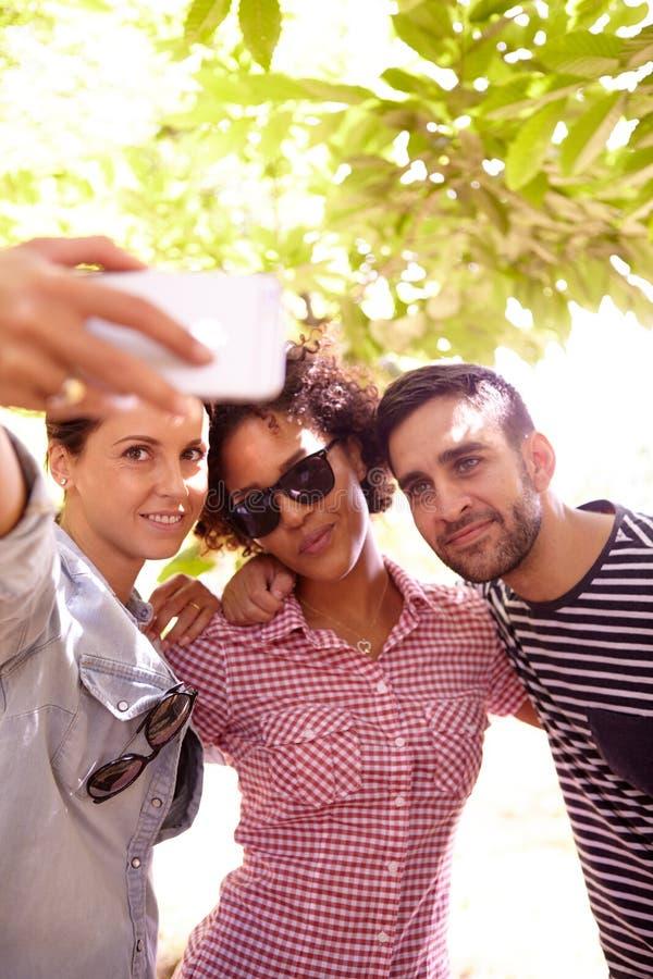 Três amigos que levantam para um selfie imagens de stock royalty free
