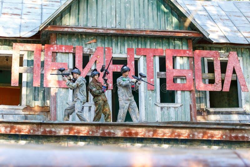 Três amigos que levantam perto do sinal gigante com paintball do texto foto de stock