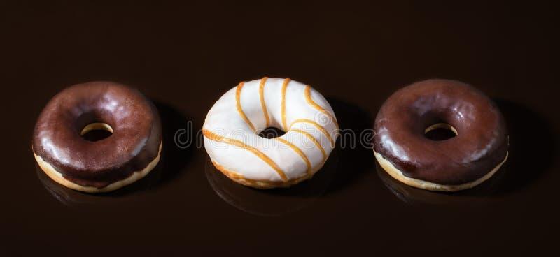 Três anéis de espuma vitrificados no fundo liso do chocolate escuro imagens de stock royalty free