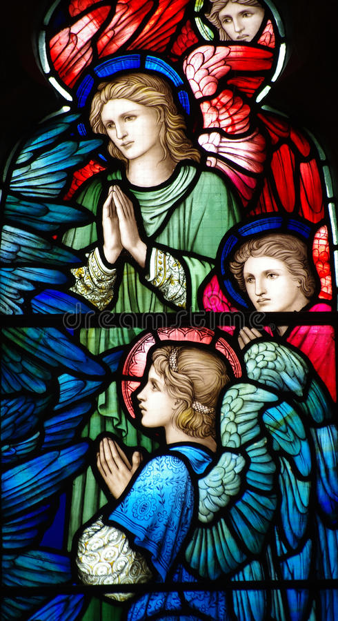 Três anjos (rezar) no vitral imagem de stock royalty free